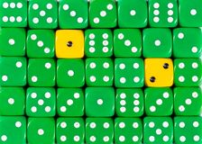 Background of random ordered green dices with two yellow cubes. Pattern background of random ordered green dices with two yellow cubes royalty free stock photo