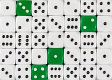 Background of random ordered white dices with four green cubes royalty free stock images