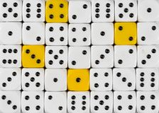 Background of random ordered white dices with four yellow cubes stock photos