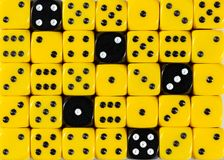 Background of random ordered yellow dices with five black cubes. Pattern background of random ordered yellow dices with five black cubes royalty free stock images