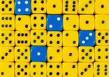 Background of random ordered yellow dices with four blue cubes. Pattern background of random ordered yellow dices with four blue cubes stock image