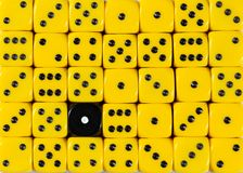 Background of random ordered yellow dices with one black cube. Pattern background of random ordered yellow dices with one black cube royalty free stock photo
