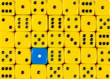 Background of random ordered yellow dices with one blue cube. Pattern background of random ordered yellow dices with one blue cube stock photography