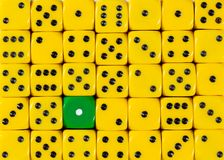 Background of random ordered yellow dices with one green cube. Pattern background of random ordered yellow dices with one green cube stock photo