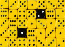 Background of random ordered yellow dices with two black cubes. Pattern background of random ordered yellow dices with two black cubes stock photo