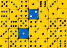 Background of random ordered yellow dices with two blue cubes. Pattern background of random ordered yellow dices with two blue cubes stock photos