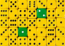 Background of random ordered yellow dices with two green cubes. Pattern background of random ordered yellow dices with two green cubes royalty free stock photography