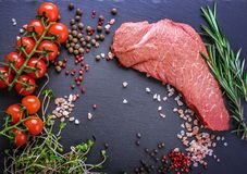 A background with a raw piece of beef and vegetables, a process. Of cooking meat with vegetable Stock Photo