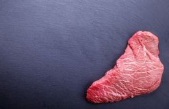 A background with a raw piece of beef and vegetables, a process. Of cooking meat with vegetable Stock Photos