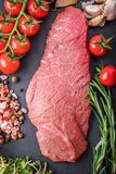 A background with a raw piece of beef and vegetables, a process. Of cooking meat with vegetable Stock Photography