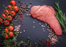 A background with a raw piece of beef and vegetables, a process. Of cooking meat with vegetable Royalty Free Stock Images