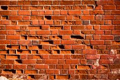 Background of a red brick wall. Old red brick wall with missing bricks Royalty Free Stock Image