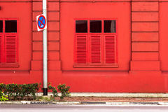 Background: Red building on the side walk with the traffic sign. Stock Photography