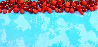 Background Red fruits and berries. Ripe red currants, strawberries, raspberries, cherries on a blue background. Berries at border royalty free stock photography