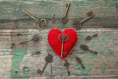 Background with red heart and antique keys on old painted wooden Stock Photos