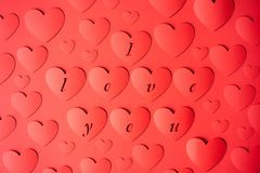 Background red hearts cut out of paper on a red background. Words I love you. royalty free stock photos