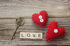 Background with red hearts and vintage key on old boards. Royalty Free Stock Image