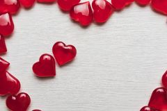 Red hearts on a white wooden substrate. Background of red hearts on a white wooden substrate Stock Images
