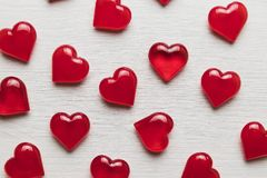 Red hearts on a white wooden substrate. Background of red hearts on a white wooden substrate Stock Photo
