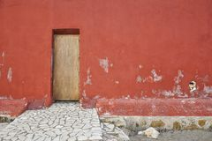 Background red old wall with wooden door. royalty free stock photos