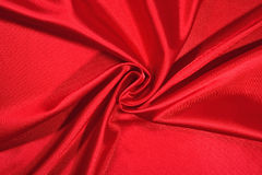 Background from a red satin fabric. With picturesque folds Royalty Free Stock Images