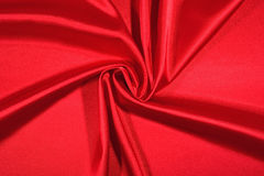 Background from a red satin fabric. With picturesque folds Royalty Free Stock Image