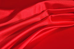 Background from a red satin fabric. With picturesque folds Stock Images