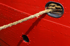 Background of red ship hull with rope. Nylon rope ties a ship to the quayside Stock Photo