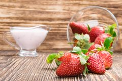Background with red strawberry and yogurt on a wooden table Stock Image