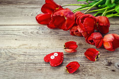 Background with red tulips and heart on grunge wooden boards. Royalty Free Stock Image