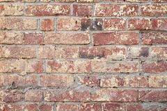 Background of red vintage brick wall, surface close-up. Colorful grunge texture of wall with peeling plaster, copy space stock image