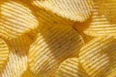 Background of ridged potato chips with spices. Closeup. Backdrop of delicious potato chips with spices. Closeup stock image