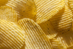 Background of ridged potato chips with spices. Closeup. Background of delicious potato chips with spices. Closeup stock photos