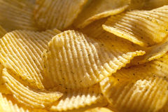 Background of ridged potato chips with spices. Closeup. Background of delicious potato chips with spices. Closeup royalty free stock image