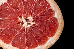 Background of ripe grapefruit Slice on black, fresh fruit texture closeup Royalty Free Stock Photos