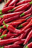 Red chili peppers. Background of ripe red chili peppers with leaves Royalty Free Stock Images