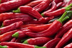 Red chili peppers. Background of ripe red chili peppers with leaves Stock Photo