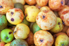 Background of ripe slightly spoiled colorful apples. Stock Photos