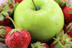 The background of the ripe strawberry and green Apple. Royalty Free Stock Images
