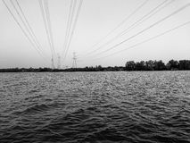 Background of River view with Power Distribution line cross the river . Black and white tone royalty free stock photography