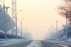 The background, road on an empty street in the city at cold winter day covered with snow near stadium, aerial Stock Photo