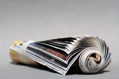 Background Rolledup magazine. Gray background magazine Stock Photos