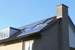 Roof of modern house with alternative solar energy, Netherlands. Roof of a modern house with solar panels and a blue sunny sky, Netherlands. Solar energy is an Stock Images