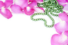 Background with rose petals and heart bead Stock Photography