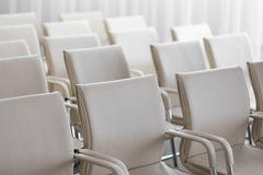 Background of row of white seats. Empty chairs in the conference hall.  Stock Photos