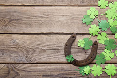 Background with rusty horseshoe and paper clover leaves on the o royalty free stock image