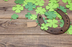 Background with rusty horseshoe and paper clover leaves on the o stock images
