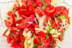 Background of the salad with tomatoes and onion. Background of the vegetable salad of a fresh sliced tomatoes, white bell pepper, onion and potherb in a glass Royalty Free Stock Image