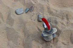 The background of a sandy beach with balanced zen stones and hot red pepper Royalty Free Stock Photo