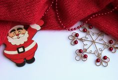 Background with Santa Claus and a beautiful metal snowflake witRed knitted, knitted tightly on a light background with red beads. royalty free stock images